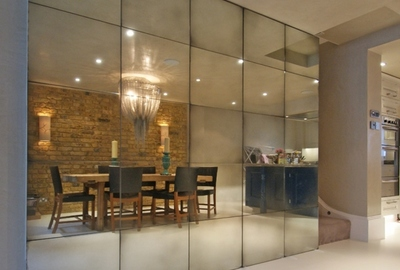 Private residence Kensington. Medium antique mirrored wall concealing folding doors for understair storage.